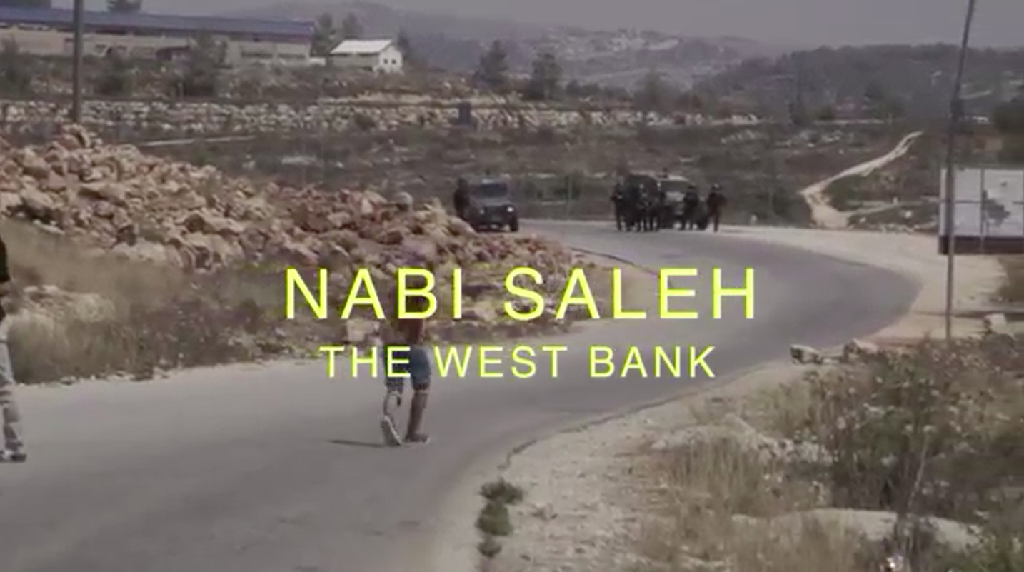 Screenshot from 'Discarding Gaza' showing a Palestinian stone-thrower facing Israeli soldiers