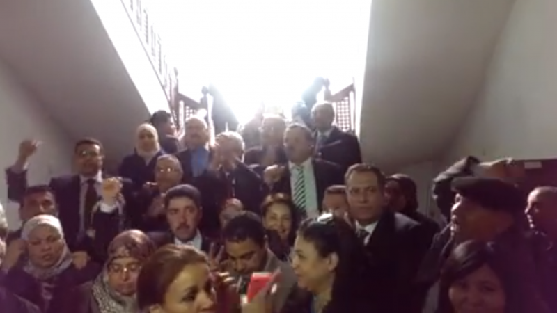 Tunisian MPs sing the national anthem during parliament lock down. [Screen shot of the video as Facebook's video embed feature messes up the post]
