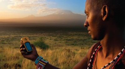 Lion Guardian Ng'ida takes a GPS point in front of Mt. Kilimanjaro. GPS data help Lion Guardians track animals and keep livestock out of harm's way. Photo by Philip Briggs.
