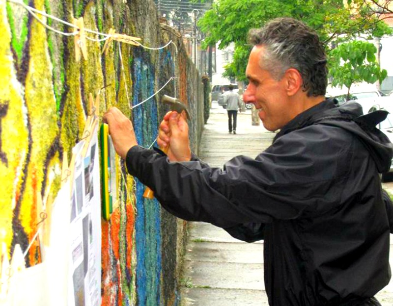 Ricardo Fraga hanging the pictures people drawn at the wall in Vila Mariana. Photo: ARTICLE 19/Facebook
