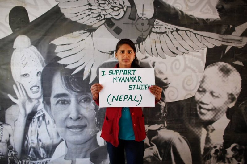 A young person from Nepal holds a placard expressing support to Myanmar student protesters