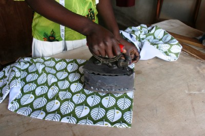 A friend in Tanzania presses a garment with a hot coal iron, in lieu of an electric one. Photo by Pernille.