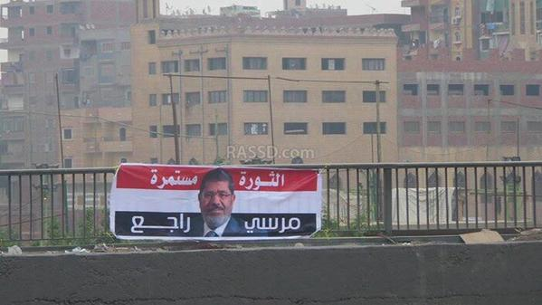 "A banner which reads: ""The revolution continues; Morsi will be back,"" seen in Giza this morning. Photograph shared on Twitter by @Ikhwanweb, the Twitter account of the Muslim Brotherhood in Egypt"