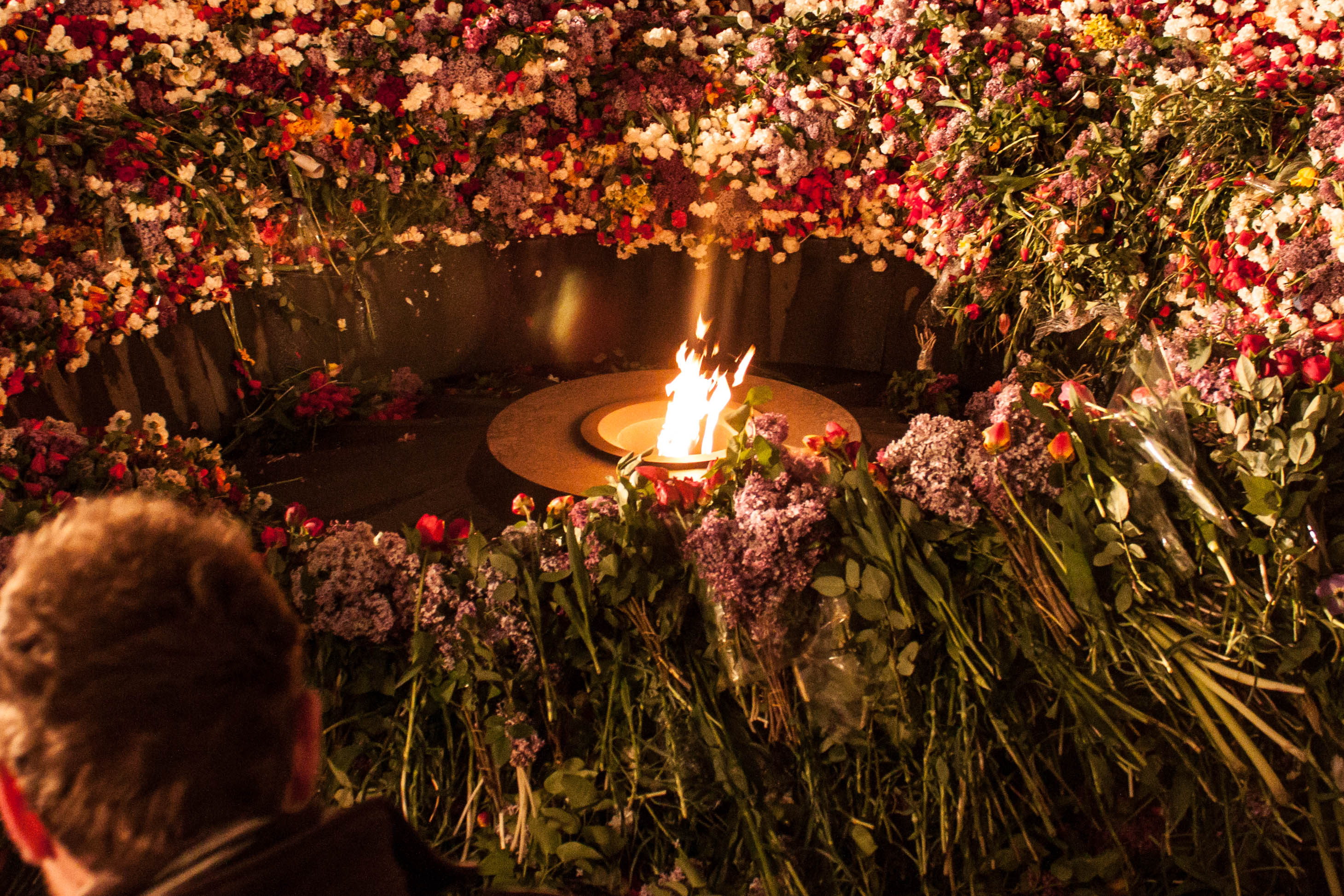 The eternal flame is seen as a man lays a flower inside Tsitsernakaberd, April 24th. Photo Taken by Joey Ayoub.