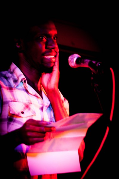Gerry Bukini, steps on stage reciting a poem in Swahili. Blinded by the red spotlight, he tries to focus on the audience while he clicks his poem forward on his mobile phone screen. 'I didn't know I could write poems in my own language' he says in a break between performances.