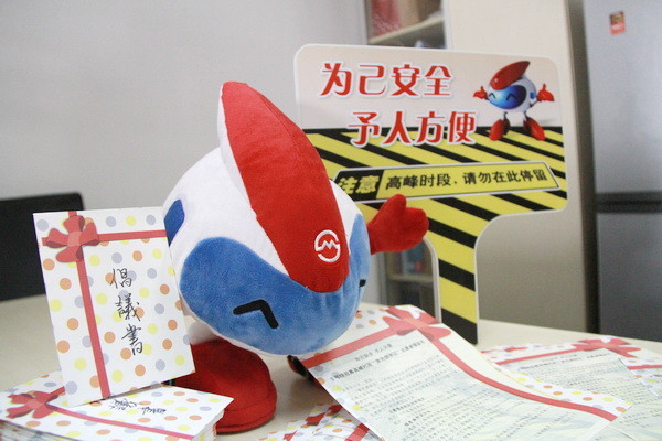 "A Chang Chang toy poses with fan letters and next to a safety sign normally posted near the track that reads ""For your personal safety and convenience, please don't loiter here during high traffic areas."" Image from SHMetro."