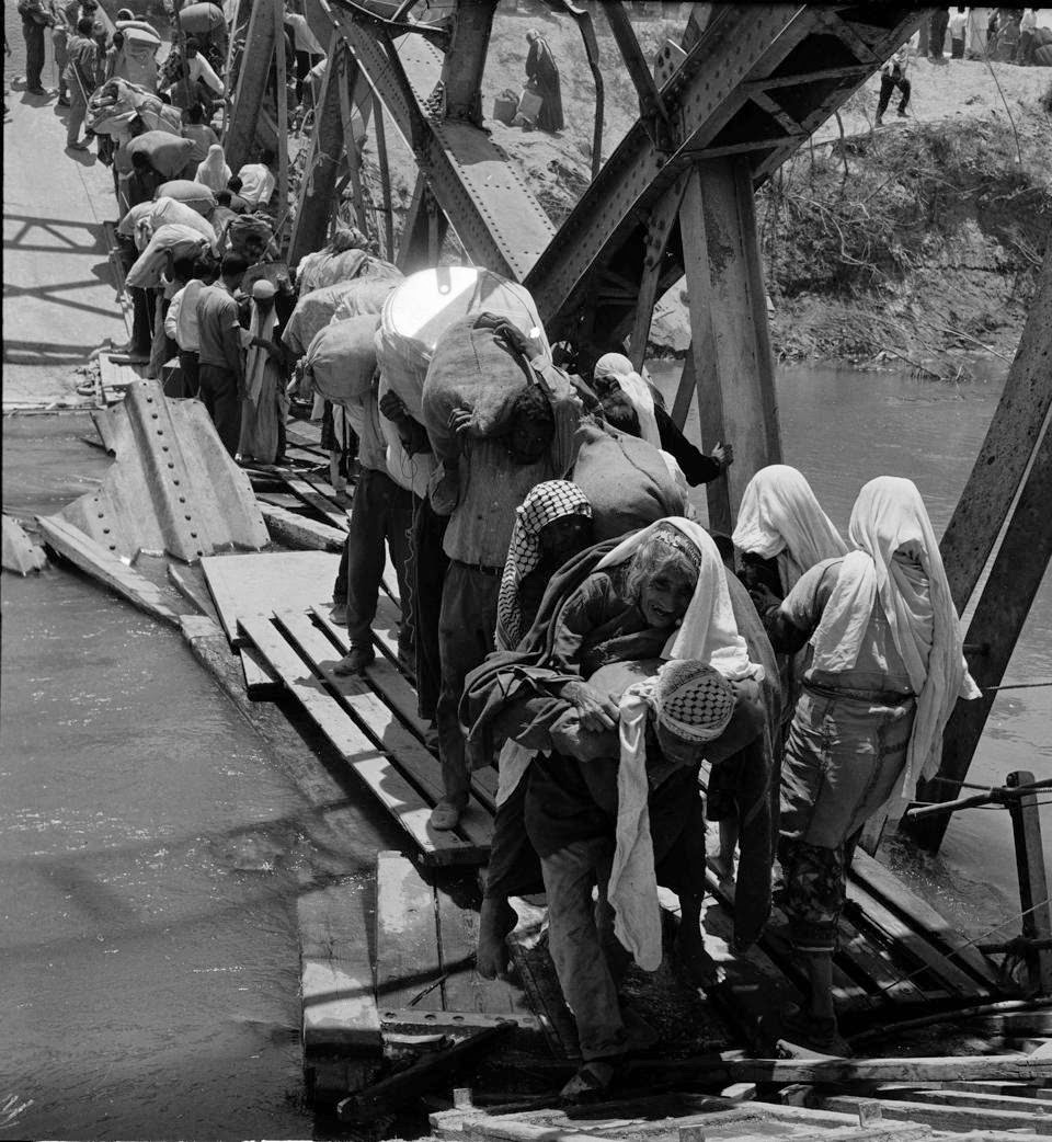 Palestine refugees flee across over the Jordan river on the damaged Allenby Bridge during the 1967 Arab-Israeli war. (UNRWA archives)