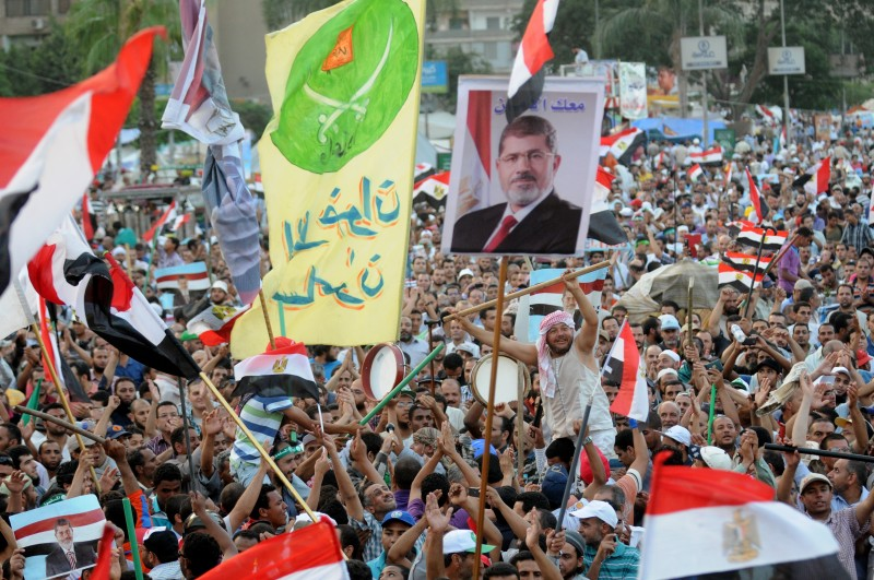 Cairo, Egypt. 1st July 2013 -- Supporters of Egypt's Islamist President Mohammed Morsi wave national flags and his posters during a rally in Nasser City, in Cairo, Egypt, before he was ousted. Photograph by Mohamed Mostafa. Copyright: Demotix