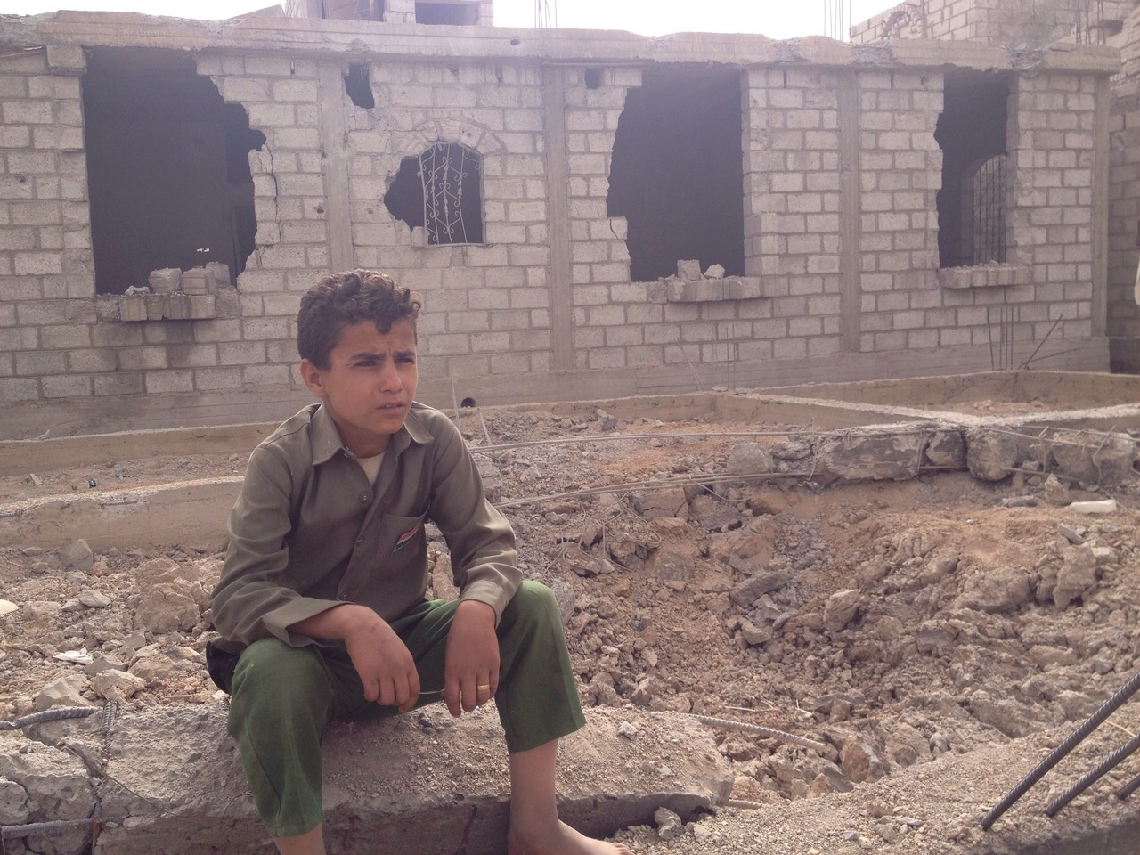 A young boy, who was luckily in school during the aerial attack by Saudi-led forces, sits outside his home on debris.r, 90KM south of Sanaa the capital of Yemen, in the afternoon hours on Tuesday, April 14, 2015.