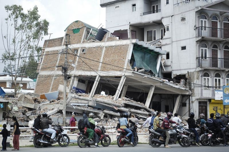 Motorcyclists drive next to debris of collapsed houses in Bhaktapur, Nepal. Image by Sunil Sharma. Copyright Demotix (15/5/2015)