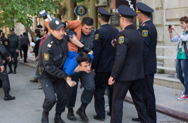 Police in Azerbaijan detain a young man. Photo by Radio Free Europe/Radio Liberty, reused with permission.