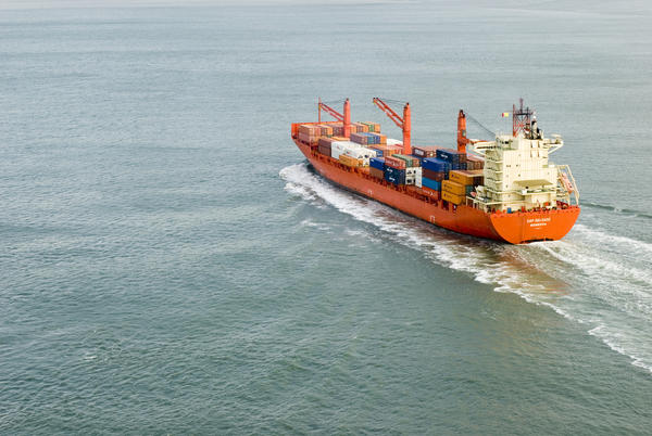 A large cargo ship full of shipping containers sailing into port. Photo: stockarch.com