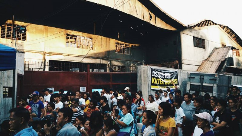 "Kentex workers, relatives of the fire victims, and supporters hold a vigil in front of the factory during the May 18 ""National Day of Mourning"". Photo Credits: Vencer Crisostomo"