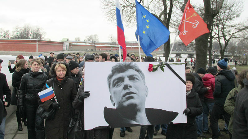 Boris Nemtsov was murdered in February 2015  before he could finish the report on the war. His photo is seen here at a memorial rally in St. Petersburg on March 1, 2015. Image from Wikimedia Commons.