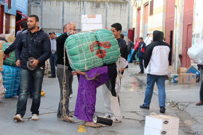 Men who work in the Spanish warehouses strap a bundle onto the back of a porteadora, so she can carry it to markets in Morocco. Credit: Maggy Donaldson. Published with PRI's permission.