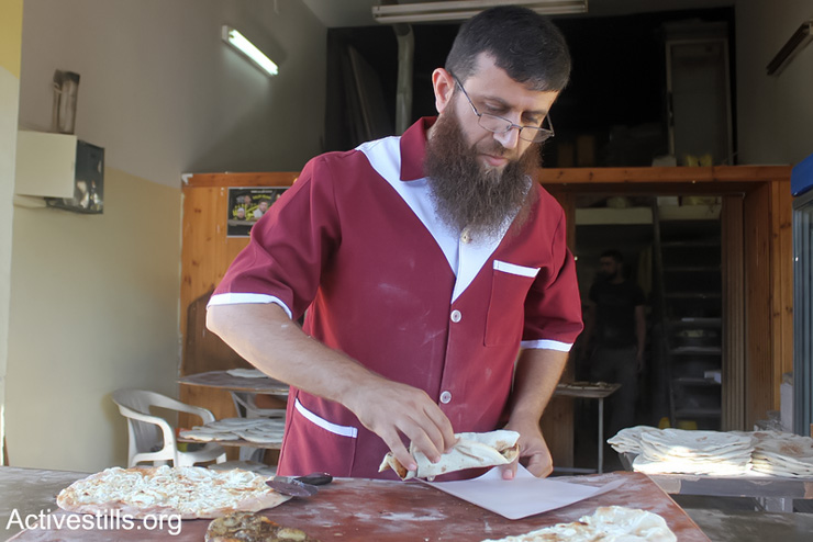 The Palestinian former prisoner Khader Adnan works at his bakery in the West Bank Village of Qabatiya near Jenin, June 21, 2013. Adnan is a former administrative detainee in Israeli jails. He was released on April 18, 2012, after being on hunger strike for 66 days. He inspired more than 1,200 Palestinian prisoners to start their own hunger strikes, For the Palestinians, he became the symbol of the hunger strike strategy. (Photo by: Ahmad Al-Bazz/ Activestills.org)