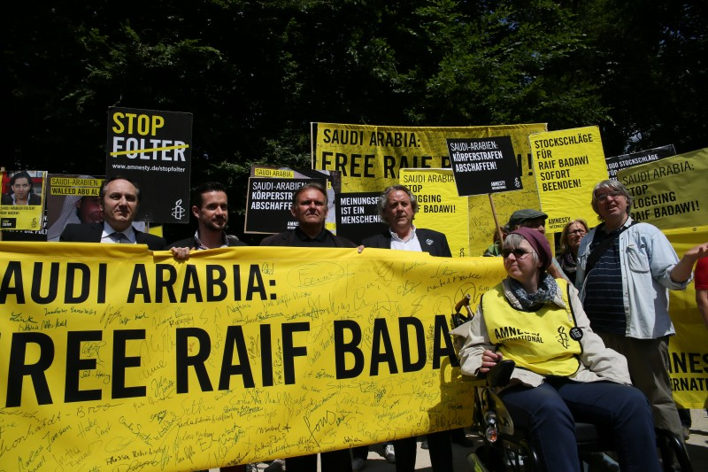Berlin, Germany. 22nd May 2015 -- Activists hold large banners and posters to demand the release of arrested Saudi Arabian blogger Raif Badawi. -- Amnesty International supported activists held a protest in front of Embassy of Saudi Arabia in Berlin, to demand the release of Saudi Arabian blogger and activist Raif Badawi, who was jailed in 2012 and sentenced to 1,000 lashes for insulting Islam. Photograph by Jakob Ratz. Copyright: Demotix