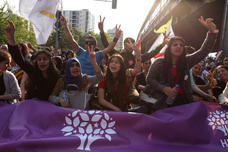 Berlin, Germany. 6th June 2015 -- Female activists shout and show the victory sign. They hold a banner with the logo of the pro Kurdish and left wing HDP. -- About 1,000 march in Berlin Neukoelln and Kreuzberg against recent bombing attacks on the election campaign of pro Kurdish HDP. The participants accuse Turkey's president Recep Tayyip Erdogan for calling his supporters for violence against HDP. Demotix image.