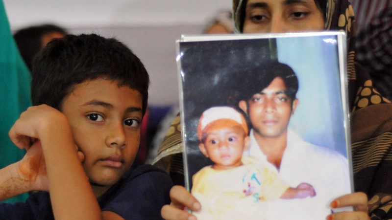 A relative holding up a portrait of the disappeared person. Image by Indrajit Ghosh. Copyright: Demotix (30/08/2014)