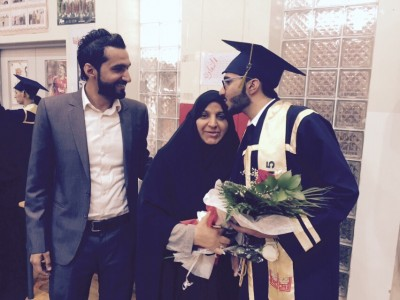 Mustafa, right, kissing his mother's forehead at the end of his graduation ceremony. His brother Ali, far left.