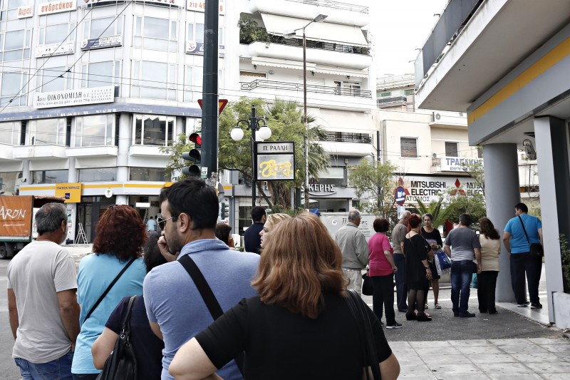 Athens, Greece. 27 June 2015 -- People line up at an ATM outside a branch of Piraeus Bank, in Athens. Photo by Alexandros Michailidis. Copyright Demotix