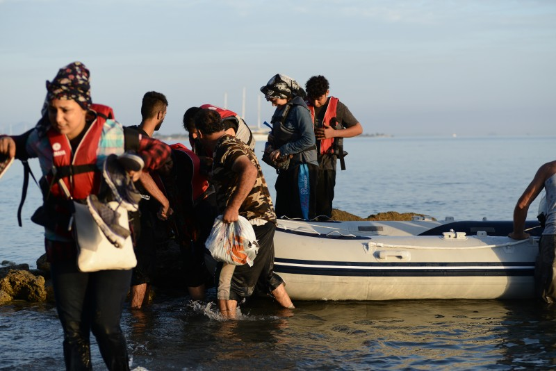 Kos, Greece. 15 August 2015 -- Syrian migrants arriving on an overcrowded dinghy along the coast of the Greek island of Kos at Psalidi beach near to the luxury hotel complexes of the island. Photo by Wassilis Aswestopoulos. Copyright Demotix
