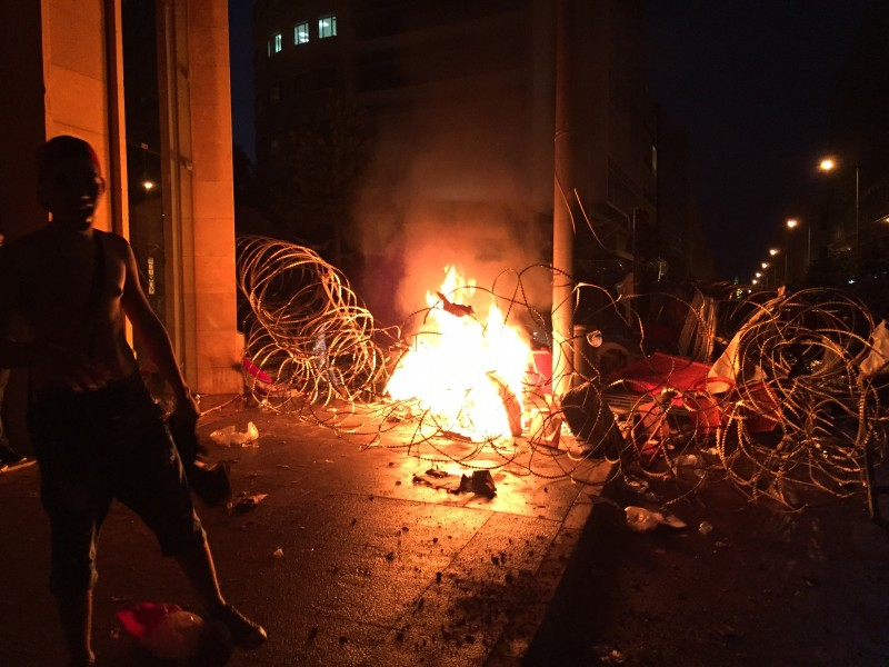 "Beirut, Lebanon. 23rd August 2015 -- A man stands next to burning barb-wire in Riad el Solh Square in Beirut, Lebanon after the army was deployed to curb the rubbish disposal protesters rallying in the capital against the government. -- Protest organized by the ""You Stink"" movement Sunday turned into violence in Beirut Riad AlSolh square after protesters started to remove the barbed wire that leads to the Grand Seraii, Lebanese government head quarters building. Photograph by Issam Abdallah. Copyright: Demotix"
