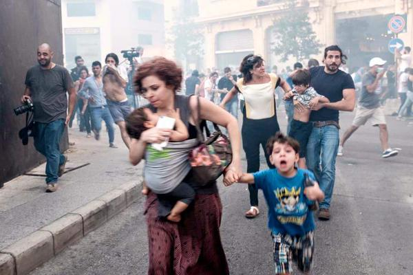 A mother and her children escape teargas fired by police on protesters in Beirut yesterday. Photograph by Sara El Ali
