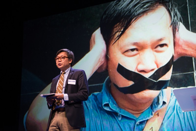 File photo of Thai journalist Pravit Rojanaphruk speaking in the 2015 Oslo Freedom Forum. He is also featured in the background photo of an anti-Junta protest demanding the protection of free speech in Thailand. Photo by Julia Reinhart, copyright @Demotix (5/26/2015)