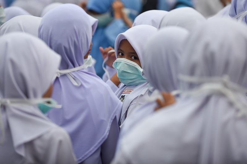 A student wears a face mask during a school assembly due to haze that hit several states in Malaysia. Photo by Fadzil Daud, Copyright @Demotix (9/13/2015)