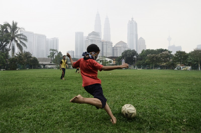 A boy covers up his face while playing football in Kuala Lumpur. The iconic buildings (Back) of Kuala Lumpur are seen shrouded by haze. Photo by Mukhriz Hazim Mohammad Zabidi, Copyright @Demotix (9/13/2015)