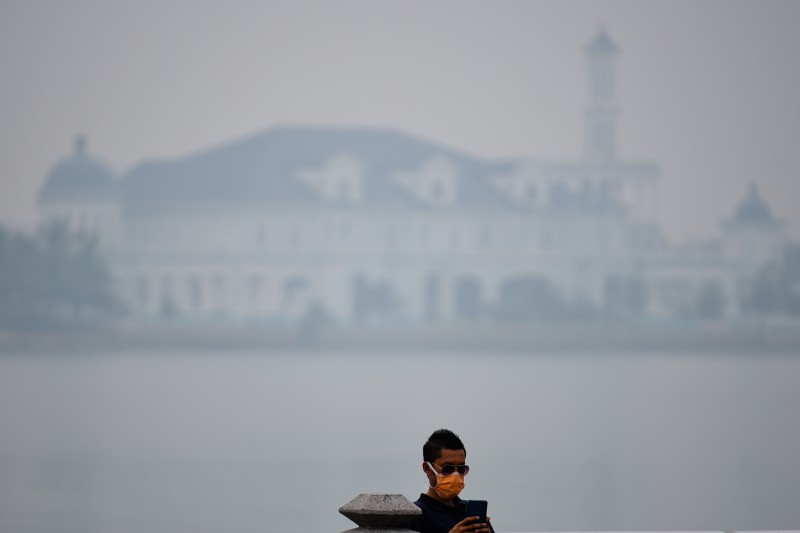 A man wears face mask checking his smartphone with a very low visibility of Sultan Ismail Mosque in Johor, Malaysia which is blanketed by a thick haze. Photo by Fadzil Daud, Copyright @Demotix (9/13/2015)