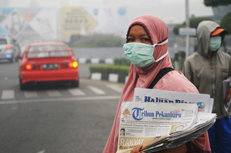 A vendor wearing a mask sells newspaper as the city of Pekanbaru in Indonesia is enveloped with haze. Photo by Fachrozi Amri, Copyright @Demotix (9/14/2015)