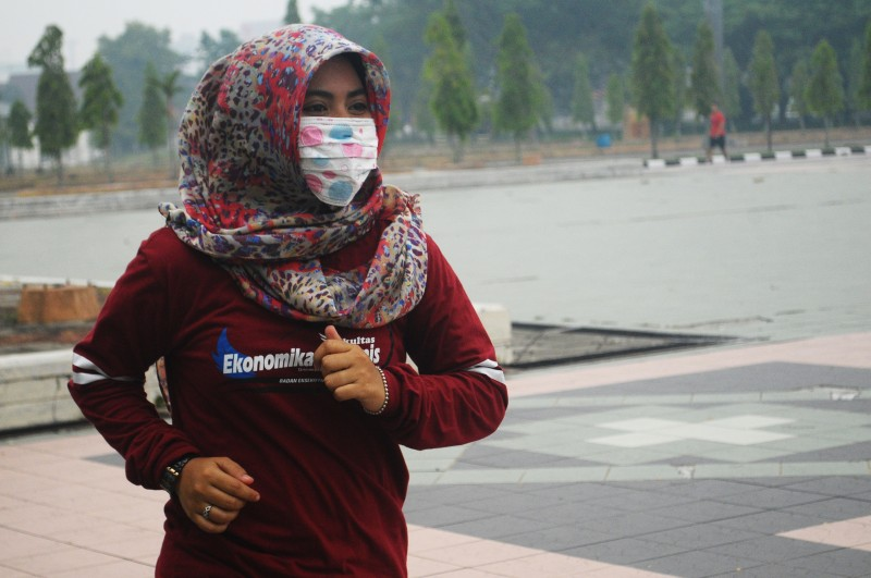 A jogger uses a mask as protection against the haze in Riau Province, Indonesia.  Photo by Fachrozi Amri, Copyright @Demotix (9/17/2015)
