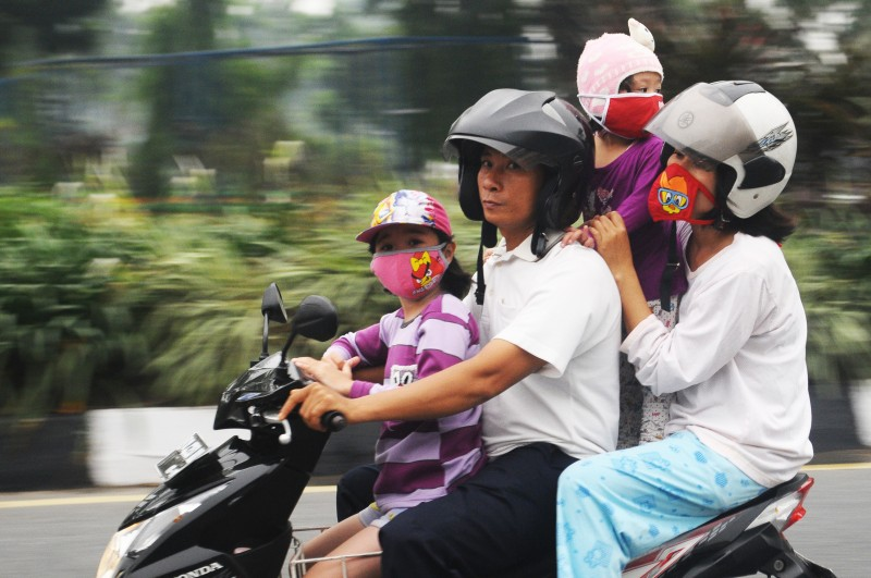 A family riding a motorcycle wear masks as protection against the haze in Riau Province, Indonesia.  Photo by Fachrozi Amri, Copyright @Demotix (9/17/2015)