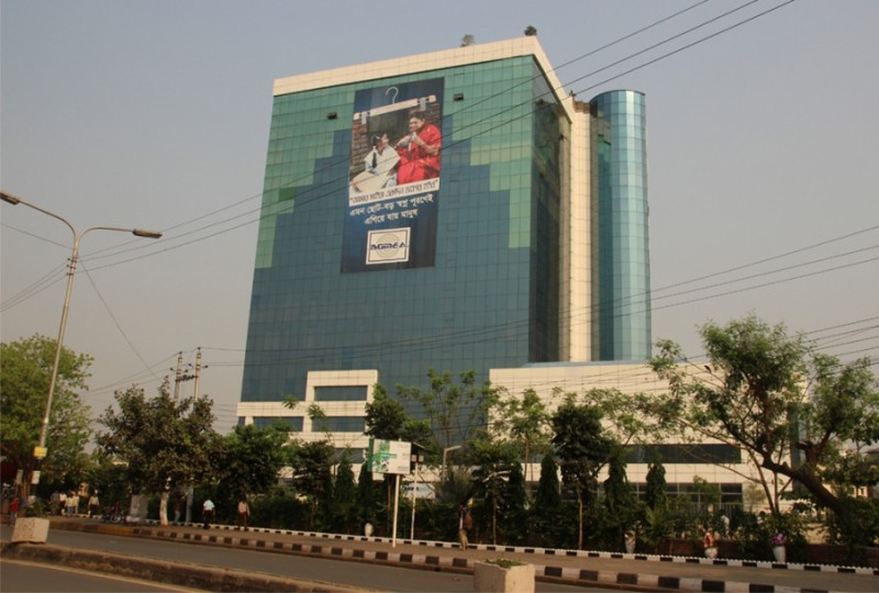 The offices of the Bangladesh Garment Manufacturers and Exporters Association, or BGMEA, tower above Dhaka. Four years ago, Bangladesh's High Court has ruled that the building was built without proper approval and in an environmentally inappropriate place, and ordered it removed. It has not been. Credit: Bruce Wallace. Used with PRI's permission