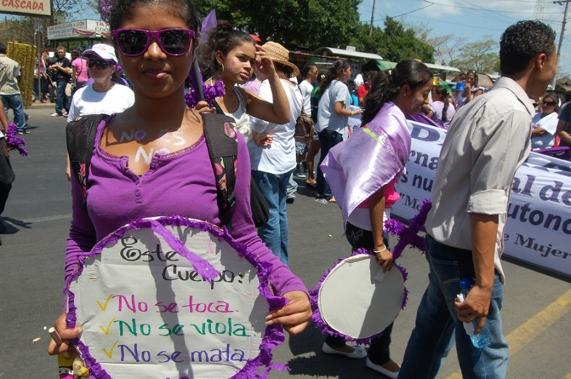 "A young activist marches on International Women's Day in 2012 with a sign that reads, ""This body will not be touched, will not be raped, will not be murdered.""  Since Law 779 was passed in 2012, it has been modified to allow mediation. Credit: Sara Van Note. Used with PRI's permission"