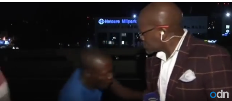 A screenshot of video footage showing Vuyo Mvoko, a South African TV reporter, being robbed at gunpoint seconds before going live on air in South Africa.