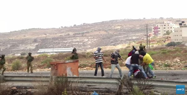 The undercover Israeli protesters seen pointing guns at Palestinian stone-throwers in a still from a video taken by AFP and shared on YouTube today. Still shared by @joeyayoub on Twitter