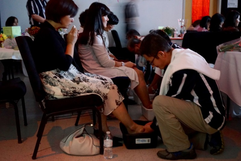 At the Father School graduation, men wash their wives' feet, just as Jesus washed the feet of his disciples in the Bible. Credit: Heidi Shin. Used with PRI's permission