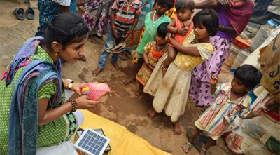A volunteer shows local residents a Polllinate Energy solar power system. Photo by Didem Tali.