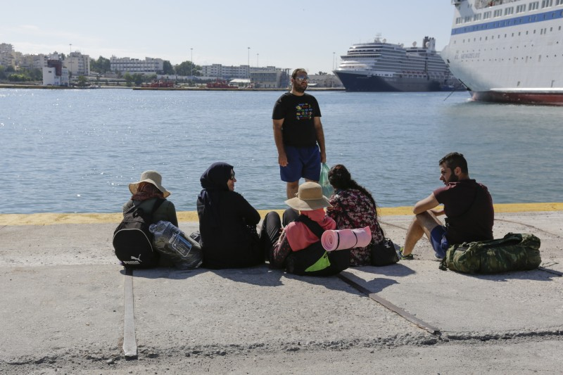 A family of refugees sits on the ground in Piraeus Harbour, watching out towards the sea, waiting for the bus to bring them to the metro station. Photo by Michael Debets Copyright Demotix (28/9/2015).