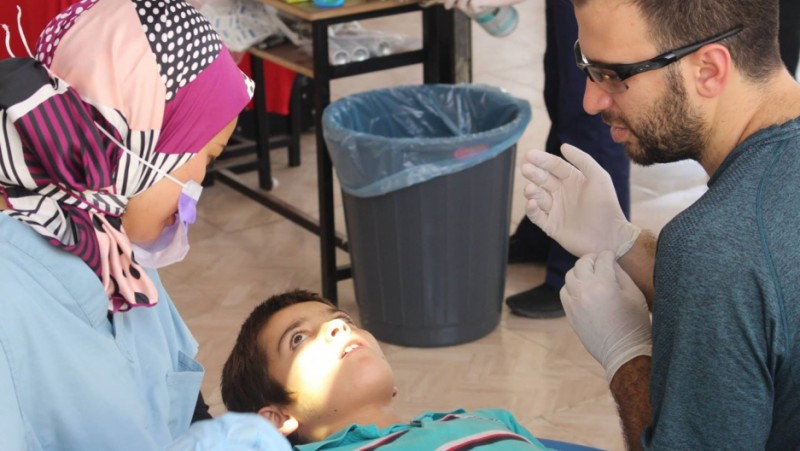 "Whether to say ""needle"" or ""sleepy juice"": Dr. Sarah Aref and Farris Barakat help a Syrian boy at the temporary Syrian American Medical Society dental clinic on the Turkish-Syrian border. Credit: Jorge Valencia. Used with permission."