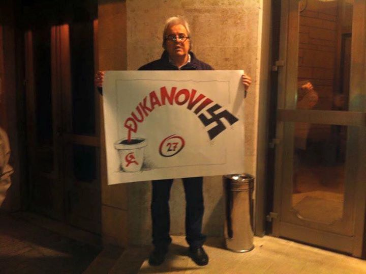 A protester in Montenegro holds an illustration that symbolizes Djukanović's almost 27 years of rule in the country - from his beginnings in the former Yugoslavia's communist party to the stronghold he has on the country today that many have called fascist.