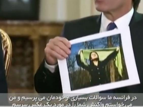 "French journalist David Pujadas shows Rouhani a picture of an Iranian women from the mandatory hijab protest page ""My Stealth Freedom."" Screenshot of interview."