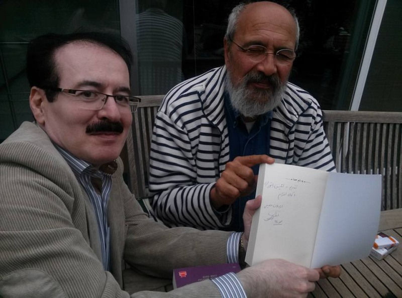 "Enis Batur, the Turkish poet, poses with Arslan Fasihi, the Iranian translator, and a signed copy of Batur's ""Bitter Knowledge"", which Fasihi translated to Persian."