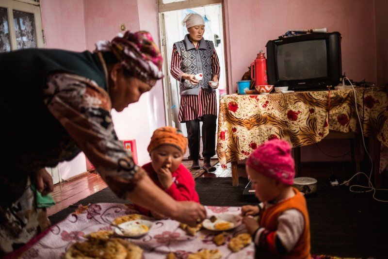 """Tologon, 63 years old, takes care of her two grandchildren, one six months old, the other two years old. """"They often talk to their mother on the phone,"""" she says. """"I say [to the children] that their mother will arrive in the summer. When summer comes, I say she will come in the winter, and she'll bring a lot of money..."""" Aravan rayon, Osh oblast."""