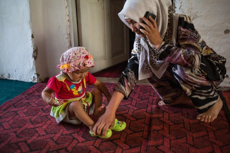 A 14-year-old girl takes care of her older sister's daughter. The older sister was divorced and went to Russia to find work. Karabag village, Batken oblast.