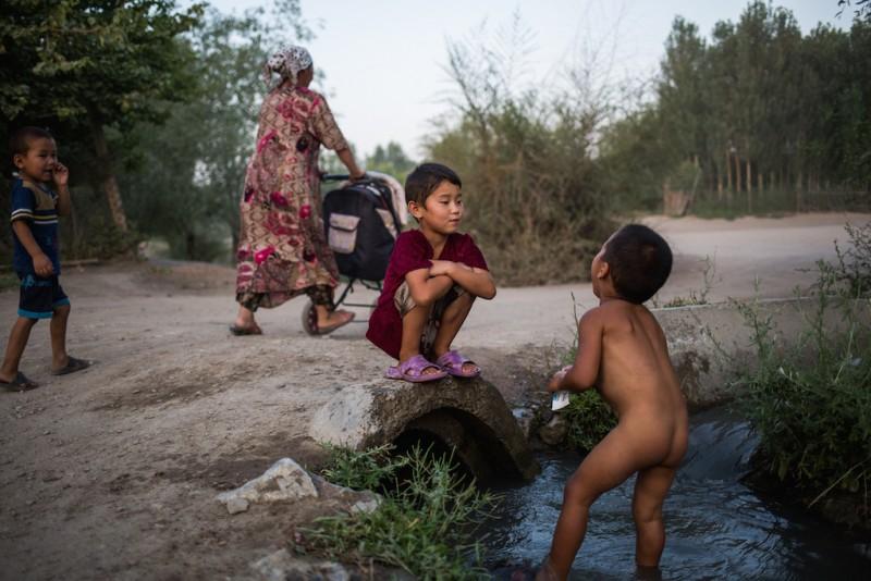 The chidren of migrant workers bath in an aryk (stream) near their house. Chek village, Batken oblast.