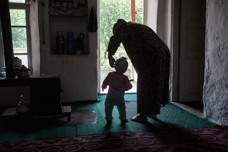 """Tolokon, 53 years old, has not seen her husband for over seven years. According to Tolokon, he went to Russia for work but has never been able to send money back. She has raised their three children alone. The eldest daughter herself divorced and moved to Russia, leaving behind a six-month-old daughter for Tolokon to raise. """"My granddaughter often says, 'Mom-Mom, Dad-Dad,' and her father, although he lives in a nearby village, doesn't visit his daughter, he is already married again..."""" Karabag village, Batken oblast."""